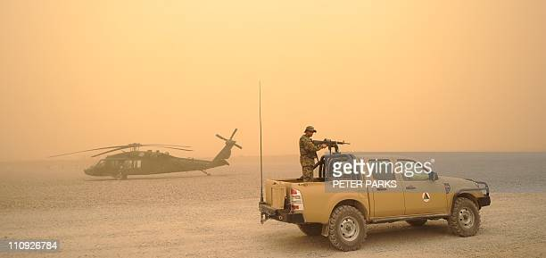 An Afghan National Army vehicle drives past a US army Blackhawk helicopter from Alpha Company 7101 AVN during a sandstorm at FOB Wilson in Kandahar...