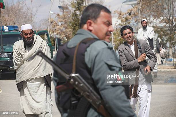 An Afghan National Police officer stands guard at the gate of the provinial office complex which houses the office of Haji Niyaz Mohammad Amirii...