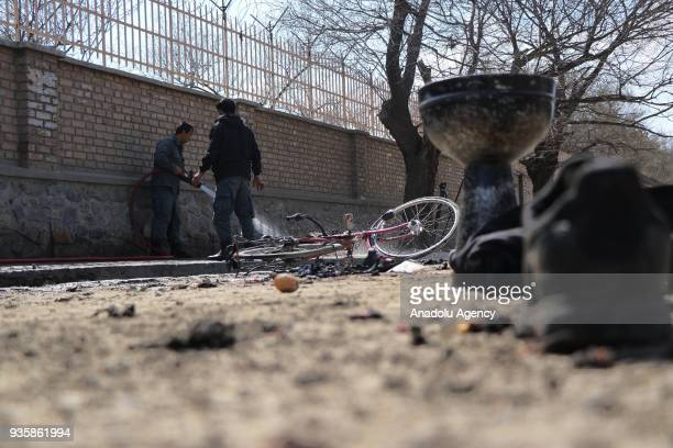 An Afghan official cleans the explosion site after a suicide bomb blast that targeted a shrine visited by Shi'ite Muslims as the country observes the...