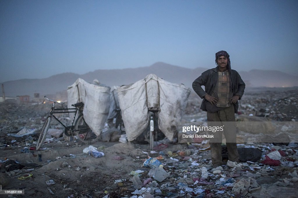 An Afghan Pashtun boy, who said he was forced from the troubled province of Baglan due to threats from the Taliban, looks on as as he scavenges for recyclables at a garbage dump site on November 14, 2012 in Kabul, Afghanistan. Children working at the garbage site in Kabul said they can make up to 90 Afghans (USD $1.75) per day collecting cans and other recyclable materials for sale. If they were to stay and work in their home province, with limited options for employment, and join the Police or Army, the Taliban threatened they would come for them and their families, they said.