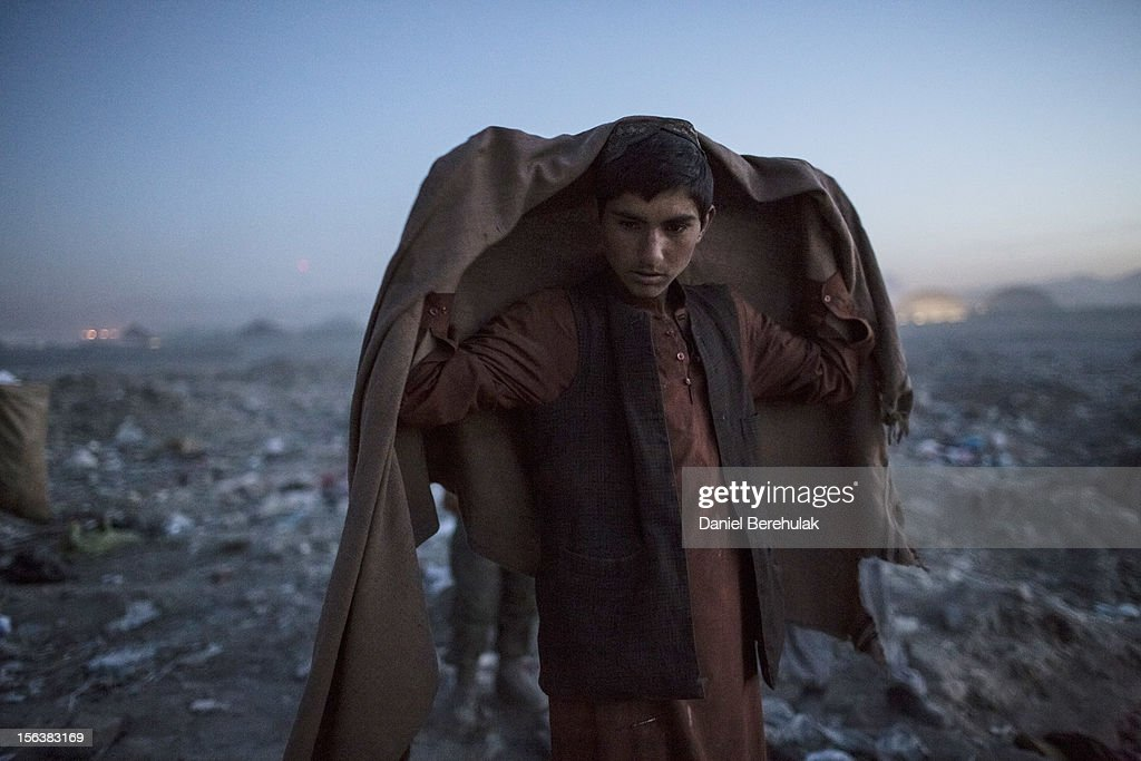 An Afghan Pashtun boy, who said he was forced from the troubled province of Baglan due to threats from the Taliban, looks on as he winds up for the day after scavenging for recyclables at a garbage dump site on November 14, 2012 in Kabul, Afghanistan. Children working at the garbage site in Kabul said they can make up to 90 Afghans (USD $1.75) per day collecting cans and other recyclable materials for sale. If they were to stay and work in their home province, with limited options for employment, and join the Police or Army, the Taliban threatened they would come for them and their families, they said.