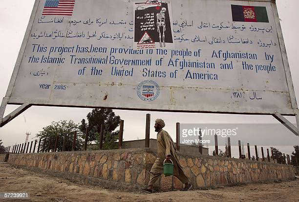 An Afghan passes a billboard with an antidrug poster on April 1 2006 in Lashkar Gah in the Helmand province of southern Afghanistan Afghan forces are...