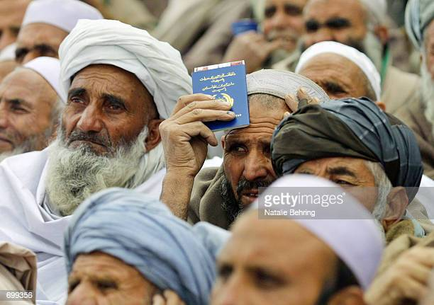 An Afghan pilgrim holds his passport as he waits with hundreds of others gathered outside Kabuls Airport to board flights to Saudi Arabia to partake...