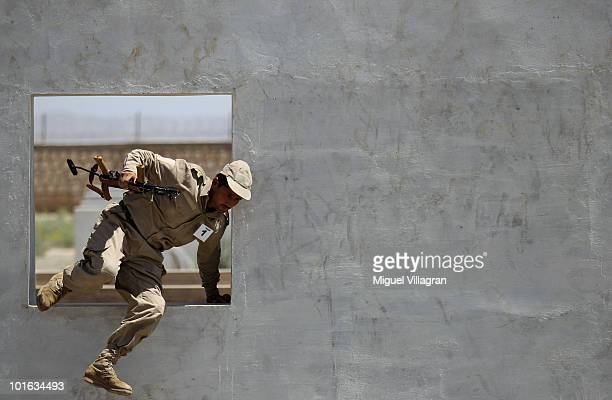 An Afghan police man jumps through a hole in a wall during a six week training program run by German police men on June 5 2010 in Kunduz Afghanistan...