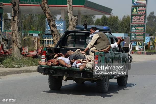 An Afghan police ranger car drives victims away after a suicide car bomb targeted a NATO convoy in Jalalabad city on April 10 2015 A suicide car bomb...