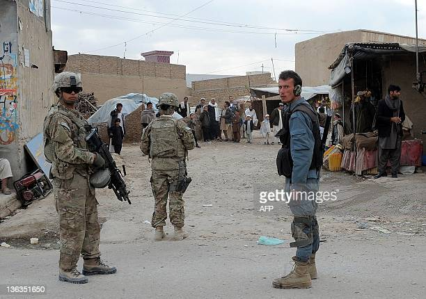 An Afghan policeman and US soldiers block a road near the scene of a suicide attack in Kandahar on January 3 2012 A suicide bomber on a motorbike...