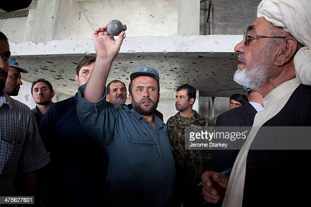 CONTENT] An Afghan policeman holds up a hand grenade which was discovered under the body of a dead insurgent in a building used to launch an attack...