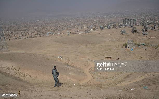 An Afghan policeman keeps watch as relatives dig a grave for one of the 27 victims killed in a bloody mosque bombing in Kabul on November 23 2016 An...