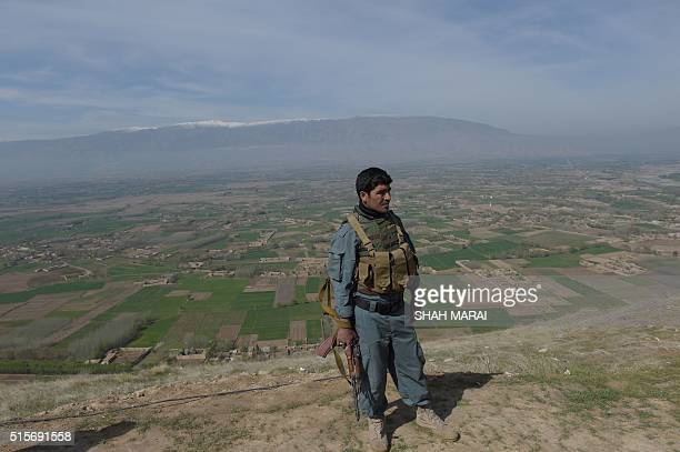 An Afghan policeman looks on in DandeGhori district in Baghlan province on March 15 following weeks of heavy battles to recapture the area from...