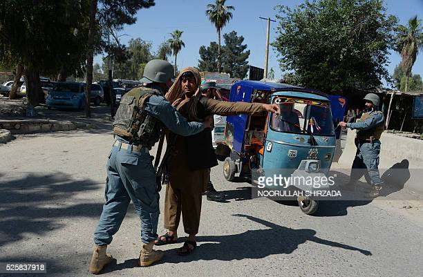 An Afghan policeman searches a passenger in the city of Jalalabad close to the border with Pakistan on April 29 after reports that an aid worker from...