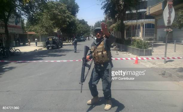 An Afghan policeman sets up a perimeter at the site of an explosion in Kabul on July 31 2017 A series of explosions and the sound of gunfire shook...
