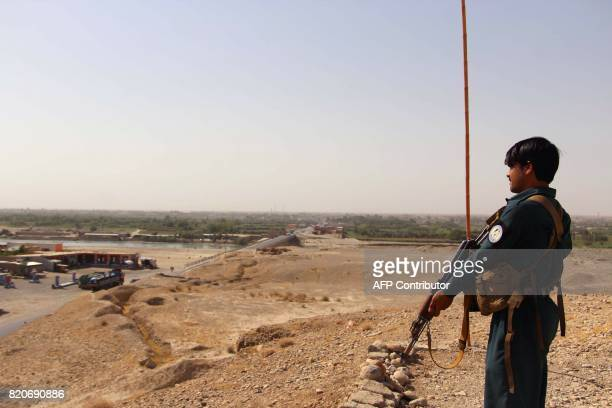 An Afghan policeman stands guard as he keep watches amid an ongoing battle with Taliban militants in the Gereshk district of Helmand province on July...