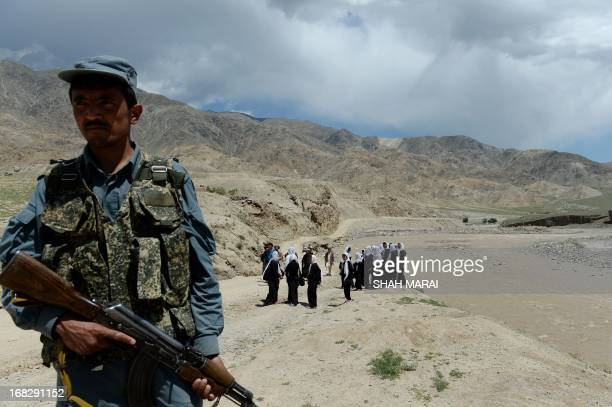 An Afghan policeman stands guard as schoolgirls wait for a bus in Qara Zaghan village in Baghlan province on May 7 2013 Afghanistan's education...