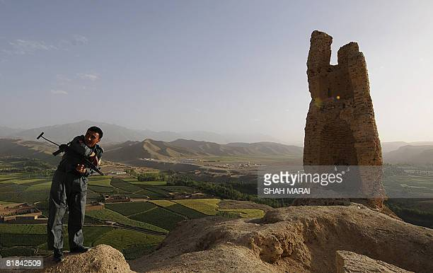 An Afghan policeman stands guard at ShahreGholghola on a hilltop over looking Bamiyan on July 6 2008 The cavemonasteries of Bamiyan and the niche...