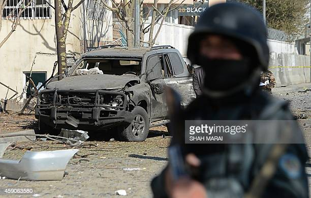 An Afghan policeman stands guard at the site where a suicide bomber targeted a vehicle convoy of Afghan lawmakers in Kabul on November 16 2014 A...