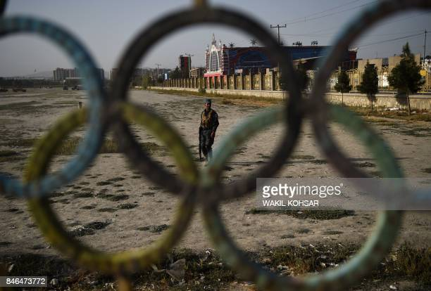 TOPSHOT An Afghan policeman stands guard near the site of suicide bomb attack on the proximity of the Kabul International Cricket ground in Kabul on...
