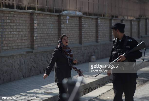 An Afghan policeman stops a woman following a suicide bombing attack in Kabul on March 21 2018 A suicide bomber on March 21 killed at least 26 people...