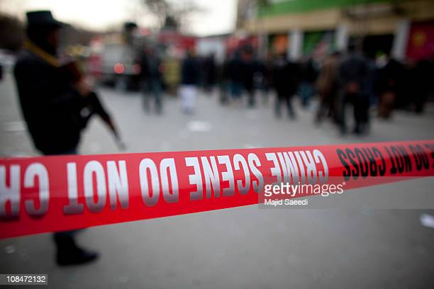An Afghan policeman walks over shards of glass and paper at the site of a suicide attack near 'Finest' supermarket on January 28 2011 in Wazir Akbar...