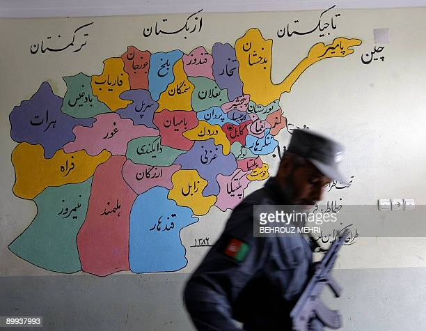An Afghan policeman walks past a map of Afghanistan at a polling station in Herat on August 20 2009 Afghans voted to elect a president for just the...