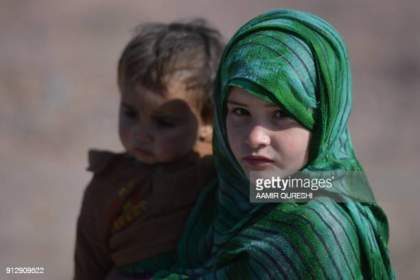 TOPSHOT An Afghan refugee girl carries her brother at a refugee camp on the outskirts of Islamabad on February 1 2018 Nearly 14 million Afghan...
