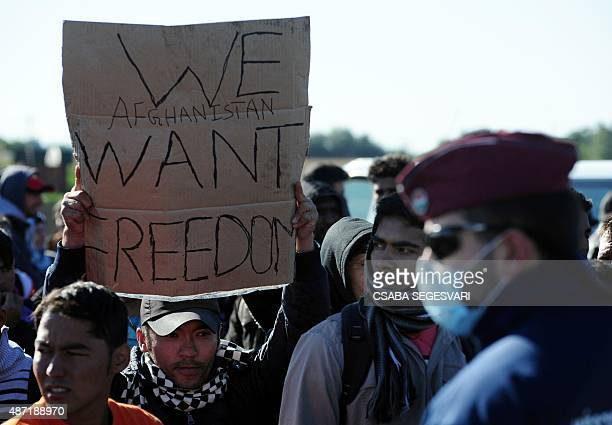 An Afghan refugee holds a handmade placard reading 'We Afghanistan want freedom' as police officers control migrants at the collection and...