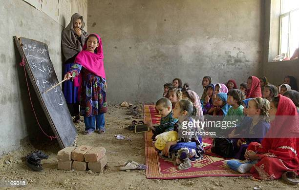 An Afghan refugee student reads Arabic script from the blackboard October 18 2001 at the Shamshatu Afghan refugee camp in Pakistan near the border of...