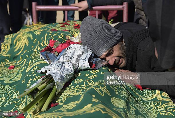An Afghan relative reacts alongside the body of Saeed Jawad Hossini who was killed in a suicide attack on a minibus carrying employees of Afghan TV...
