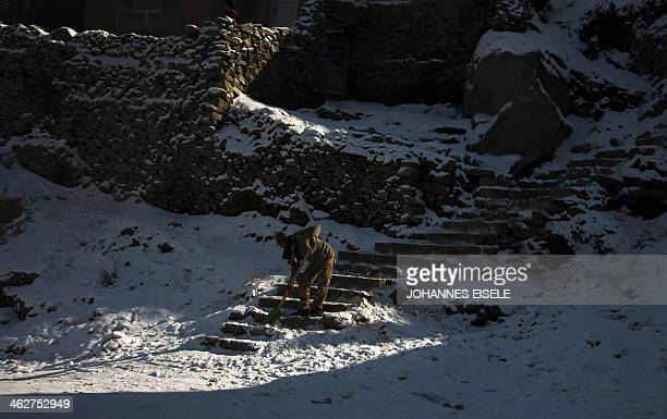 An Afghan resident clears snow from the stairs in front of his house in Kabul on January 9 2014 As winter sets in across Central Asia many Afghans...