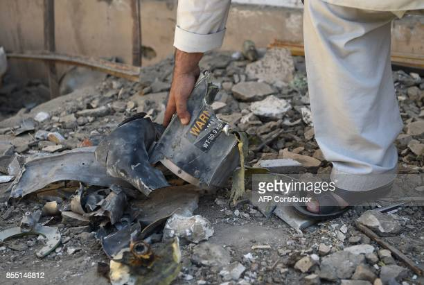 An Afghan resident collects pieces of shrapnel in a damaged courtyard following a NATO airstrike on a house in Kabul on September 28 2017 NATO's...