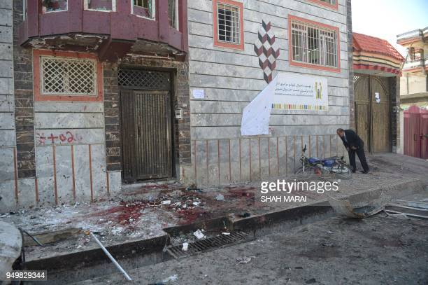 An Afghan resident inspects the site of a suicide bombing outside a voter registration centre in Kabul on April 22 2018 A suicide bomber blew himself...