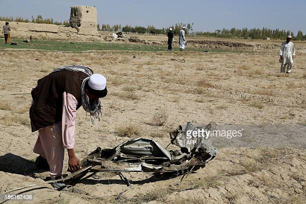 An Afghan resident lifts a piece of mangled wreckage from a vehicle at the scene of a blast in Ghazni on October 28 2013 A roadside bomb on October...