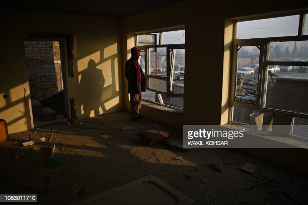 An Afghan resident looks through broken windows of a damaged shops near the site of a powerful truck bomb attack a day after it detonated near a...