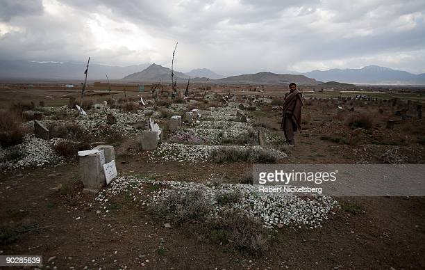 An afghan resident of Deh Sabs village north of Kabul Afghanistan stands near the graves of fighters from Pakistan's militant group HarikatulAnsar on...