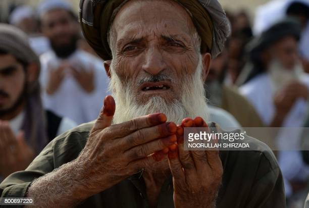 An Afghan resident offers prayers at the start of the Eid alFitr holiday which marks the end of Ramadan at open air mosque on the outskirts of...
