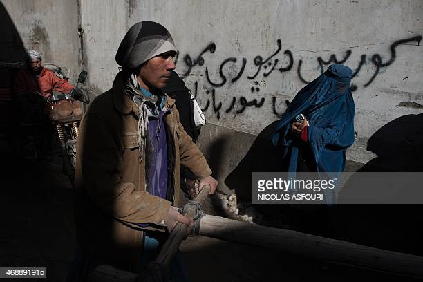 An Afghan resident pushes a cart past grafitti reading Mahmoozai Driving School as a motorcyclist and a pedestrian make their way along a street in...