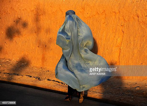 An Afghan resident walks along a road in Herat province on August 16 2014 Afghanistan's economy has improved significantly since the fall of the...