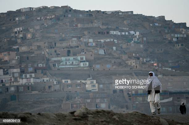 An Afghan resident walks along a road near a livestock market in the outskirts of Kabul on December 28 2013 Hundreds of traders gather daily at the...
