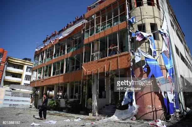 An Afghan resident walks in front of a damage wedding hall building near the site of a car bomb attack in western Kabul on July 24 2017 At least 24...