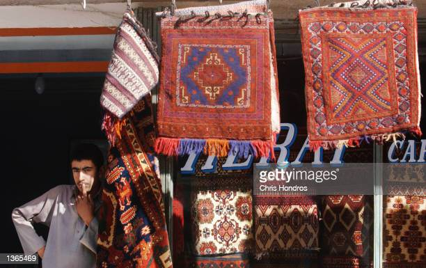 An Afghan rug merchant looks out of his shop on the commercial hub on Chicken Street September 3, 2002 in Kabul, Afghanistan. Life and business goes...