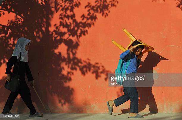 An Afghan schoolboy carries a chair towards a class in an open area in Mazar-i Sharif, capital of the Balkh province on April 9, 2012. At the start...