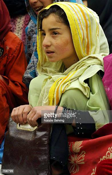 An Afghan schoolgirl cluthes her purse as she recites the letters of the Dari alphabet at the Amir Dost Mohammad Khan Secondary School on the first...
