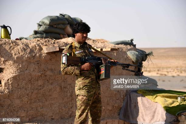 An Afghan security force keeps watch at a checkpoint in Maiwand district of Kandahar province on November 14 2017 Dozens of Afghan police and...