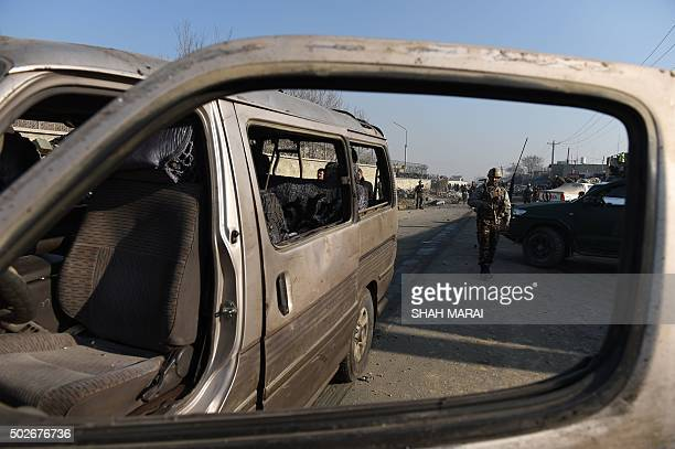 An Afghan security force member inspects the site of a suicide car bomb near the international airport in Kabul on December 28 2015 A Taliban bomber...
