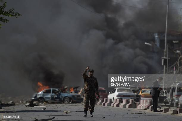 An Afghan security force member stands at the site of a car bomb attack in Kabul on May 31 2017 At least 40 people were killed or wounded on May 31...