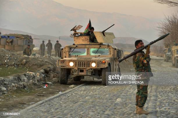 An Afghan security force personnel holds a rocket-propelled grenade near the site of a car bomb attack in Sherzad district of Nangarhar Province on...