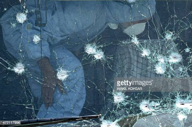 An Afghan security official inspects a bullet riddled windscreen at the scene of a suicide attack on a bus that was transporting employees of the...