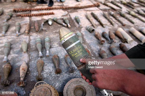 An Afghan security official inspects confiscated ammunition explosives and arms recovered from the outskirts of Herat March 3 2010 in Herat...