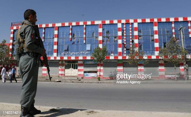 An Afghan security official stands guard after an overnight suicide bomb blast that targeted a wedding reception in Kabul Afghanistan on August 18...
