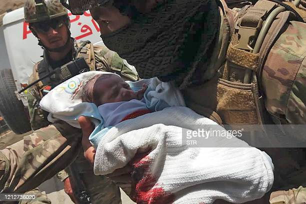 TOPSHOT An Afghan security personnel carries a newborn baby from a hospital at the site of an attack in Kabul on May 12 2020 Gunmen stormed a...