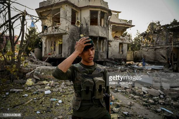 An Afghan security personnel gestures as he stands guard at the site a day after a car bomb explosion in Kabul on August 4, 2021. / The erroneous...